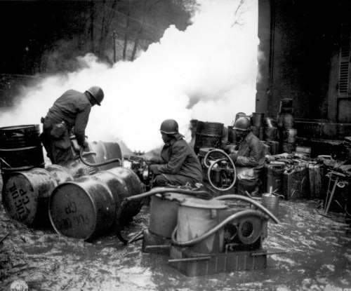 """Soldiers of the 161st Chemical Smoke Generating Company, U.S. Third Army, move a barrel of oil in preparation to refilling an M-2 smoke generator, which spews forth a heavy cloud of white smoke. These men are engaged in laying a smoke screen to cover bridge building activities across the Saar River near Wallerfangen, Germany."" - December 11, 1944 From: The National Archives"