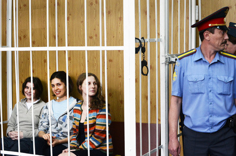 "Putin's Religious War Against Pussy Riot The pretrial hearings in the case of Pussy Riot, a Russian female punk band, are held behind closed doors in a Moscow court. Police have cordoned off not only the courthouse itself but also the street outside to keep the band's supporters from even coming close to the building. Any attempt to hold a sign or chant is stopped; policemen grab the offenders and throw them into avtozaks (police buses). The three band members, Nadezhda Tolokonnikova, twenty-three; Maria Alekhina, twenty-four; and Ekaterina Samutsevich, twenty-nine—Nadia, Masha, and Katya—are being prosecuted for an unsanctioned ""punk-prayer"" called ""Our Lady, chase Putin out."" The women managed to perform for about thirty seconds in the Moscow Christ the Savior Cathedral before the church's security guards kicked them out. A music video using the footage shot in the cathedral was distributed on the Web. For that, the three women have been kept in pretrial detention since March; on Friday last week, the judge extended their incarceration for six more months, and yesterday their trial was scheduled for July 30th. They are facing up to seven years in prison. The prosecution of the Pussy Riot women is more than an act of absurd injustice and cruelty; it is a sign that the Russian state is increasingly lashing out against those citizens it sees as overly modernized. Vladimir Putin has often said that modernization is the goal of his regime, but its policy is increasingly slipping toward something egregiously anti-modern, obscurantist, even medieval. The Pussy Riot case is a telling illustration of Putin's political crackdown—and of his increasing reliance on the Russian Orthodox Church as a resort of the most conservative societal forces. Before their arrest, Tolokonnikova was a student of philosophy; Alekhina studied journalism and creative writing and was engaged in religious charities and environmental causes. Samutsevich, the oldest of the three, has a degree in computer programming. They are members of a larger group that also goes by the name Pussy Riot—they use a transliterated version of the English words—that combines radical performance with leftist ideas ranging broadly from anti-authoritarianism to feminism; the group cites figures such as Michel Foucault and Julia Kristeva among their many sources of inspiration, as well as the American punk-rock band Bikini Kill and the riot-grrrl movement of the nineties. Tolokonnikova and Alekhina are mothers of young children whom they have not seen since their arrest.  Technically, the three women are prosecuted for hooliganism; a more appropriate definition of their offense would be contempt of high authority. The Pussy Riot's ""punk prayer"" was blatantly disrespectful of both Putin and the patriarch of the Russian Orthodox Church. The secular and the clerical leaders share a sense of mutual loyalty. Each of them presides over a heavily centralized, hierarchical power realm; both are intolerant to those challenging their authority. ""The regime is demonstrating an attempt to evolve toward religious fundamentalism,"" wrote Nikolai Svanidze, a prominent media figure. He referred to this trend as ""a little bit of Iran"" in Russia. Piety and faith for their own sake do not appear to be Putin's concern, however. Instead, the government is drawing on the traditionalist and anti-western attitudes of the Russian Orthodox Church as a way of cracking down on the regime's liberal opponents. Leading members of the Orthodox clergy promptly condemned the Pussy Riot performance as blasphemy and sacrilege. Tellingly, the formal, supposedly secular indictment also drew on clerical language, citing ""sacrilegious humiliation of the age-old principles aimed at inflicting even deeper wounds to Orthodox Christians""; ""deep offense and humiliation of the religious guides of the believers""; ""chaotically waving arms and legs, dancing and hopping… all with a goal to cause a negative, even more insulting resonance in the feelings and souls of the believers""; ""desecrating the cathedral, and offending the feelings of believers."" According to prosecution, there were about a dozen ""injured parties,"" most of them security guards who happened to be on duty in the cathedral during the seconds that the ""blasphemous act"" lasted, plus a sacristan and a candle-keeper. Two lawyers representing one of the security guards claim that their client, Vladimir Potan'kin, was so deeply emotionally wounded that he is now suffering from sleeping problems. In an interview with a Russian newspaper last week, Potan'kin's lawyers called Pussy Riot a ""criminal conspiracy"": ""Lurching behind [Pussy Riot] are the real enemies of our state and of the Orthodox Christianity; those who instigated this multipurpose provocation are hiding behind Tolokonnikova's group, and [there are also others] hiding behind those who are hiding behind them."" The conspiracy, according to the two lawyers, is global and overwhelming. In an interview, one said that the incident could ""soon escalate into events comparable to the explosion of the twin towers on September 11th in America… It was proven that the act had been committed not by the American government or by the C.I.A. but by forces above them. For instance, all the employees of the shopping center""—the lawyer referred to the W.T.C. as torgovy tsentr, the Russian for ""mall""—had been informed through secret masonic channels that they should not report to work on September 11th."" When the interviewer asked, ""Do you mean that the Pussy Riot act and the terrorist attack in the U.S. were organized by the same people?,"" the lawyers responded, ""In the first instance it was a satanic group, and in the second it was the global government. But at the highest level both are connected—by Satan."" Who else? The supposedly satanic schemes executed by Pussy Riot nevertheless have to be punished by a secular court. In a language worthy of the Spanish Inquisition, one of them said, ""This is what mercy is about. They should redeem their guilt here, on earth, by repentance and humility."" In the courtroom hearing last Friday, Potan'kin's lawyers spoke in much the same terms. If the judge thought it was inappropriate courtroom language she didn't say so. The case of Pussy Riot has polarized Russian society, much like the Dreyfus affair (to which it has been compared) did in the late eighteen-nineties and early twentieth century in France. Over two hundred prominent Russian culture and arts figures signed a letter expressing their outrage over the travesty of justice. Over forty-one thousand rank-and-file Russians have added their signatures. Those defending Tolokonnikova, Alekhina, and Samutsevich include believers and nonbelievers. Even among the Russian clergy there are those who raised their voices calling for mercy. But liberal priests are very few and are only found at low levels of the hierarchy. The top clergy are prominent members of the political élite, and the church and state are deeply engaged in mutually beneficial relations. Late last year, a new law handed over vast real estate to religious organizations (the Russian Orthodox church is of course the major benefactor), and Putin has promised government funding for religious schools. In return, the highest-ranking clerics have staunchly supported the government leadership and its policies. The Russian Orthodox priesthood is, on the whole, deeply conservative, with strong xenophobic and anti-western streaks. Over the past years, the top clergy mostly kept those forces quiet, so as not to compromise the state and its modernization rhetoric. But as the government set out to quash the anti-government activists, it has found the social conservatism to be useful. The end Putin seeks is to consolidate the support of the conservative majority and neutralize the modernized ones. Polarization through aggression and xenophobia is the means. And that was the trap that caught Pussy Riot. Photograph by Natalia Kolesnikova/AFP/Getty.  Read more http://www.newyorker.com/online/blogs/newsdesk/2012/07/putins-religious-war-against-pussy-riot.html#ixzz21cz5e99X"
