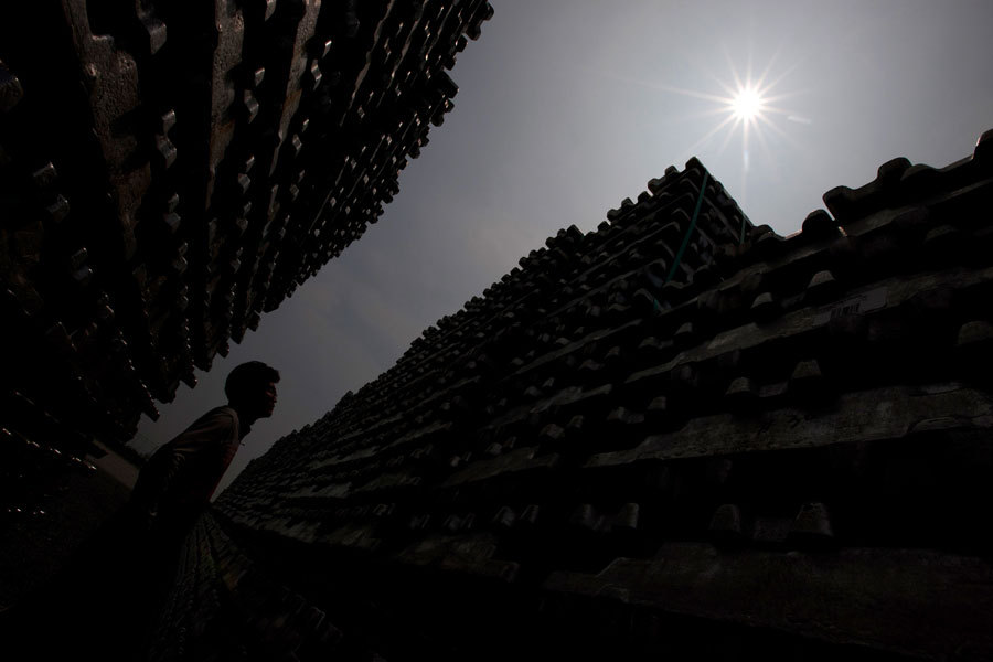 A worker inspects aluminum ingots stacked at the Public Procurement Service (PPS) Busan base warehouse in Busan, South Korea, on  July 21. Photograph by SeongJoon Cho/Bloomberg