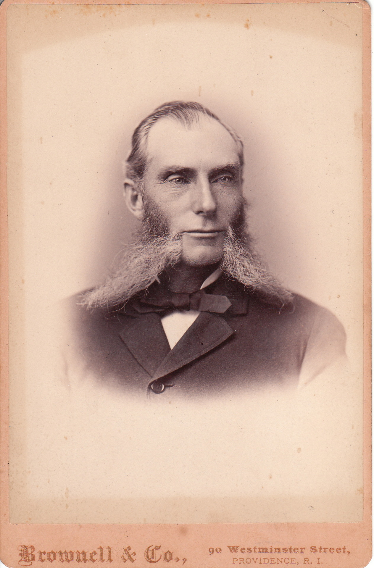 "The gentleman photographed for this cabinet card  wears his beard in a most unusual style. His place in the Cabinet Card Gallery's category of  ""Beards (Only the Best)"" is well deserved. The photographer of this portrait is Alexander C. Brownell of Providence, Rhode Island. Brownell's death notice appeared  in a 1916 photographic magazine. The article stated that Brownell died in New York City of ""hardening of the arteries"" but that his health had been less than robust for the previous 30 years due to his accidentally poisoning himself thirty years earlier while experimenting with chemicals to be used for zinc etchings.  (via)  I imagine Alexander coming home exhausted after a long day in the shop.  His wife noticing his morose demeanor grabs both of his epic chops like handles and yanks him in for a kiss."