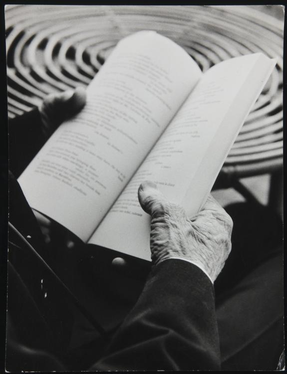 Photograph of the hands of Ezra Pound holding an open book with a table in the background