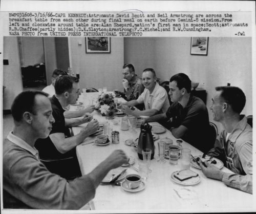 Astronauts eat breakfast on the morning of the Gemini 8 launch, 1966. Starting left and going clockwise: Alan Shepard, Dave Scott, Roger Chaffee, Deke Slayton, Neil Armstrong, Curt Michel, Walt Cunningham.