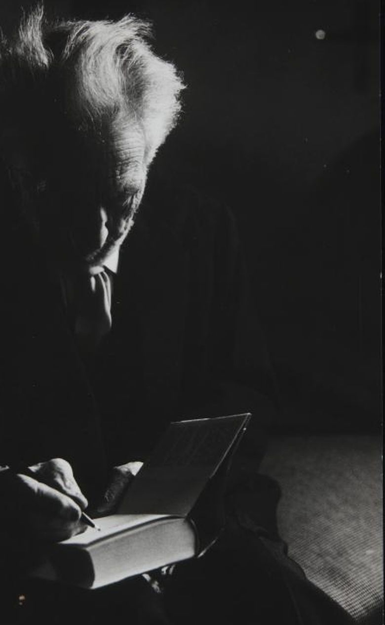 Photograph of Ezra Pound signing a book