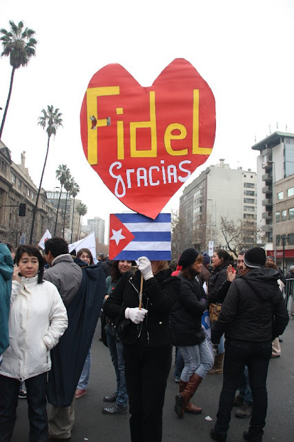 """Thanks Fidel"" The photographer quotes the woman who was carrying this sign as having told her, ""Thanks to Fidel, my son is a doctor"" June 28, 2012; Santiago Source This wouldn't be the last protest she went to."