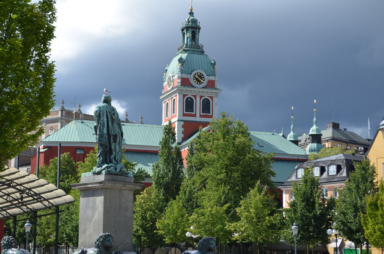 "Kungsträdgården (""King's Garden"") with Karl XIII's statue and St. James' Church against an ominous sky"