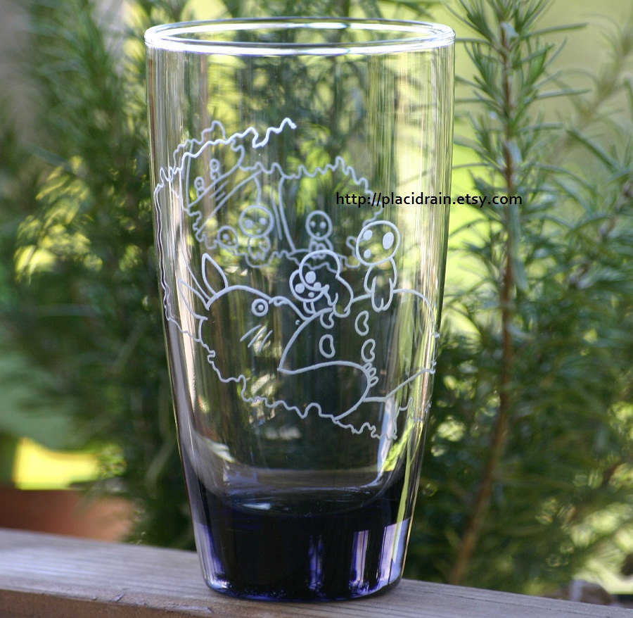 thedrunkenmoogle:  Totoro and Kodamas Etched Highball GlassCreated by Placidrain - $25 The curious kodamas from Princess Mononoke play atop a surprised Totoro on this Miyazaki mash-up glass.  I need this