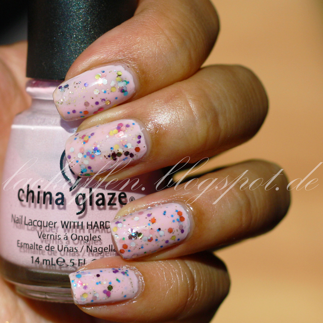 Light pink nail polish with confetti glitter