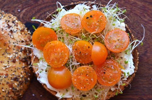 tango-mango:  Lunch. Toasted bagel with cream cheese, sprouts and orange cherry tomatoes from the garden.
