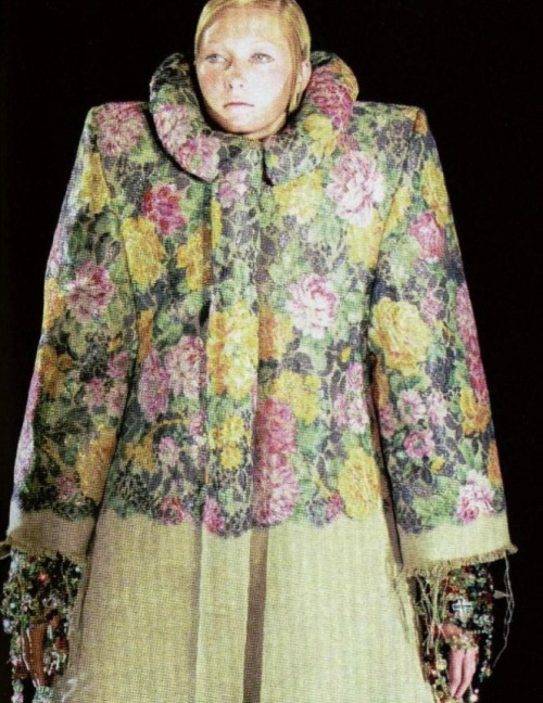 "Viktor & Rolf Haute Couture F/W 1999 ""In the winter of 1999 we appeared on the cat walk ourselves to dress a single model, Maggie Rizer, in nine layers of jewel encrusted dresses. After each layer, the small pedestal on which Maggie stood would rotate, giving the audience an opportunity to see a particular set on her before the next layer was laid on. When the final veil had been draped around her, Maggie was carrying approximately 70 kilos of richly decorated textures on her shoulders."""