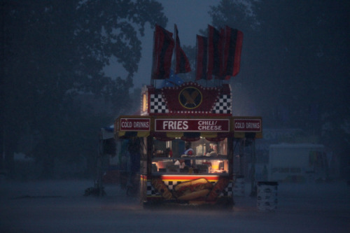 A french-fry stand illuminates the darkness that fell over the Ohio State Fair last night during a brief thunderstorm. The storm was predicted to be as severe as the June 29th monster that knocked out power across Ohio, but the heavy rain did not cause major problems. Photo by Dispatch photographer Eric Albrecht