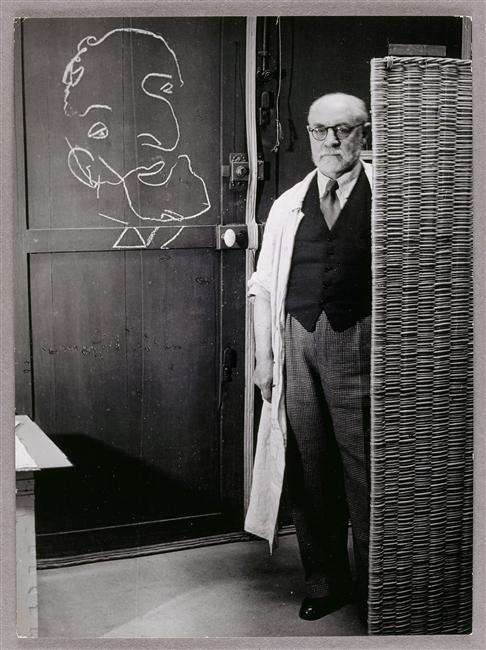 Brassaï: Henri Matisse standing against a screen and drawing with chalk, 1939.