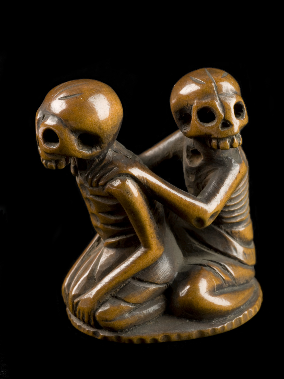 Netsuke in form of seated skeletons  Skeletons often appear in netsuke. They are sometimes in quite comic poses. This tiny wooden netsuke is in the form of two seated skeletons. The one behind has his hands on the other's shoulders. The meaning of the imagery is uncertain. The netsuke was made in Japan. Netsuke are toggle-like ornaments. They hang objects such as medicine boxes or tobacco pouches from the sash of a kimono – a traditional form of Japanese dress. Netsuke carving is a form of miniature sculpture which developed in Japan over several hundred years. They were often beautifully decorated with elaborate carving, lacquer work, or inlays and were usually made from wood, ivory or porcelain.