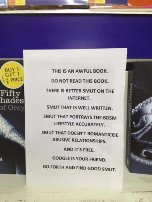 """This is an awful book"" sign in front of a bookstore display of Fifty Shades of Grey books."
