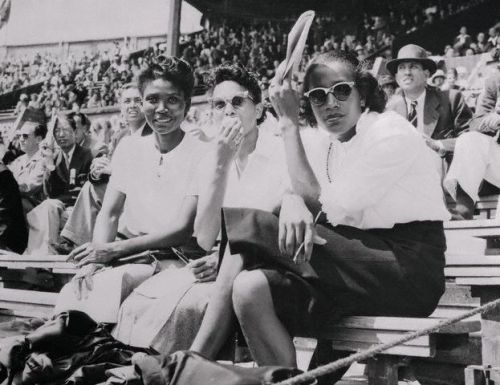 Alice Coachman (far right), the first African-American woman to win a gold medal (1948 London) takes a break and watches the games with fellow athletes, Emma Reed, of Nashville, Tennessee (broad and high jumper) and Nell C. Jackson, of Tuskegee, Alabama, (200 meters and relay. Ms. Coachman, a native of Albany, Georgia, won the gold in the high jump. Photo: Bettman/Corbis
