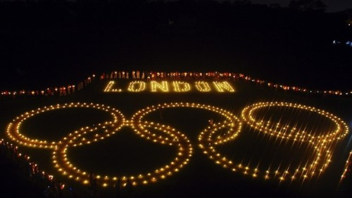 Sports students light candles to form an Olympic ring at Madan Mohan Malviya Stadium aimed at building support for Indian athletes participating in the London 2012 Summer Olympics, in Allahabad, India.