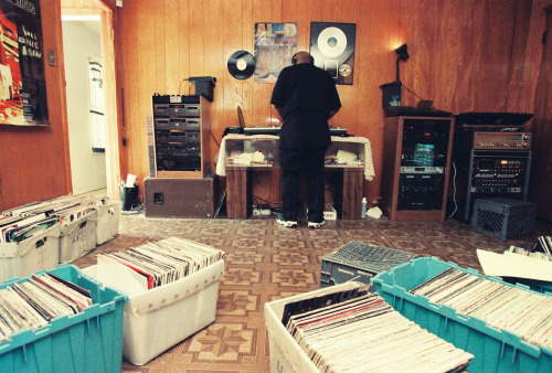 youmightfindyourself:  DJ Screw began DJing at age 12 in 1983, and started his trademark slowed-down mixes in 1990. The mixes began as special compilations requested by friends and those in the know. He soon made them available for sale when his close friend Toe offered to buy a mix from him for ten dollars. At that point, customers had increasingly begun requesting his more well-known mixes instead of personalized lists. During the early 1990s, he invited some of the Houston rappers from the city's south side to rap on those mixes. This coalition of rappers eventually became the formation of the Screwed Up Click. He moved to a house near Gulfgate Mall. Fans, some driving from far away areas such as Dallas and Waco, lined up at his door to obtain his recordings. He started his own business and opened a shop up on 7717 Cullen Blvd in Houston TX called Screwed Up Records and Tapes. It has been shown in numerous music videos and documentaries as well as independent films. There are now several Screwed Up Records and Tapes spread out through Texas, including one in Beaumont and in Austin. (Editor's note: I love this photo. It's a perfect marriage of how blurred the things that make you money and the things that make you happy can be and how it's not necessarily a bad thing.)
