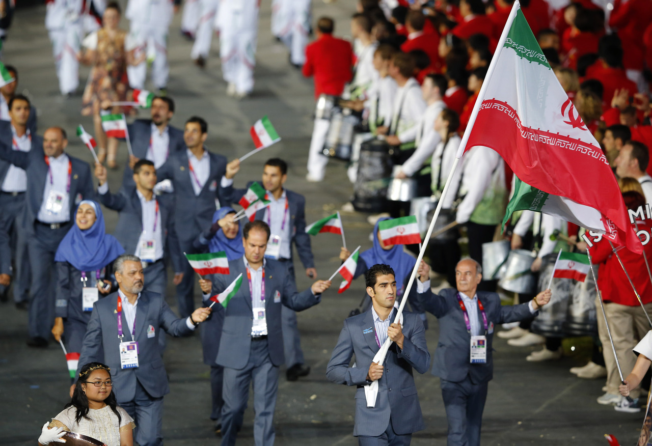 Iran's flag bearer Ali Mazaheri (C) holds the national flag as he leads the contingent in the athletes parade during the opening ceremony of the London 2012 Olympic Games at the Olympic Stadium July 27, 2012. [REUTERS/Mike Blake]