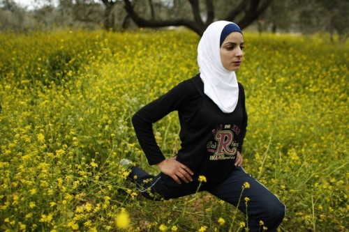 thebengalcat:  Palestinian runner Worood Maslaha, 20, stretches as she practices with her trainer Saher Jura (unseen) at a field belonging to her family in the West Bank village of Asira Ash-Shamaliya near Nablus. Four Palestinians will participate in the London Olympics and joining Maslaha will be Gaza runner Bahaa al-Farra, Cairo-based swimmer Ahmed Jabreel and swimmer Sabeen Kharyoon from Bethlehem. Picture taken March 27, 2012. (Reuters)