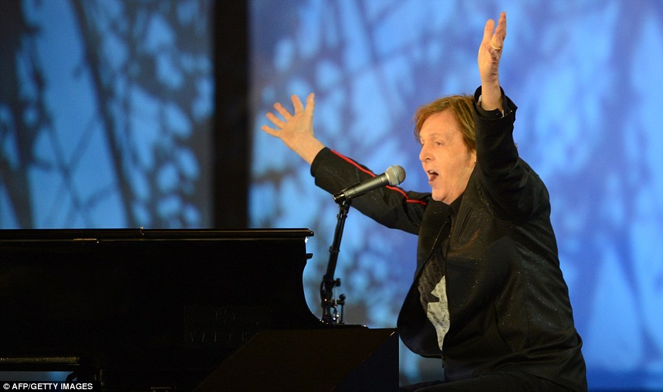 Beatles legend Sir Paul McCartney raises his arms as he sings at the end of the opening ceremony, as he brings the show to a close with a performance of Hey Jude