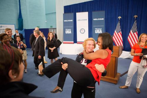 apsies:   First Lady Michelle Obama is picked up by U.S. Olympic wrestler Elena Pirozhkova during a greet with US Olympic Team athletes in London, England, July 27, 2012. (Official White House Photo by Sonya N. Hebert)