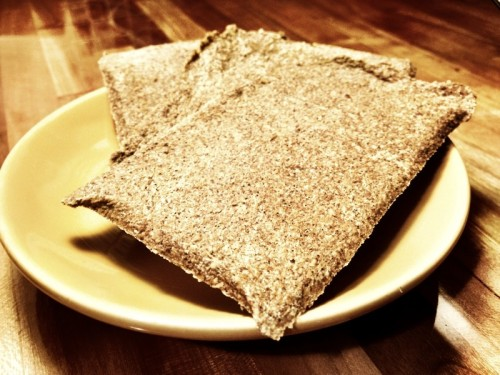 "Sweet Flax Crackers Before I went grain-free, I would indulge in a ""peanut butter Wasa cracker."" This is a simple concoction that consisted of peanut butter spread onto a Wasa Sourdough cracker and topped with a bit of honey. It also happened to be my hubby's favorite snack. Needless to say, when I went grain-free, so did the hubby. And the Peanut Butter Wasa Cracker ceased to exist. Sadly. It's been about a month without our favorite treat, but it seems like an eternity. Never fear though…. for we have discovered a recipe for a sweet cracker to replace our Wasa. It's made of flax, of course! The recipe was found on the SparkRecipes website. The photo above shows our first attempt at this cracker recipe. It took a lot longer than 25 minutes to make the crackers crisp…. and I think I see a food dehydrator in our future somewhere. Nevertheless, I think this flax cracker recipe is a fine substitute. I used honey instead of stevia (and I only used 1 teaspoon as I knew that I'd be making my hubby's favorite treat with these crackers—which is already sweetened with peanut butter and honey). Overall, I am satisfied with this sweet flax cracker recipe. I may make some tweaks next time, but it's nice to know that going grain-free doesn't have to mean giving up your favorite treats!"