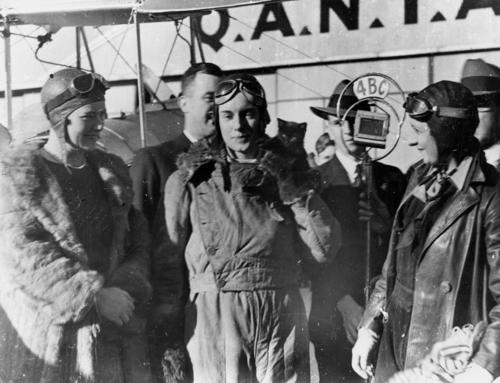 Aviatrix Jean Batten being interviewed after her flight from England to Australia by State Library of Queensland, Australia on Flickr.  Location: Archerfield, Brisbane, Australia Date: May 1934 Description: Miss Batten is pictured in the centre, holding her black kitten mascot. She is wearing her aviator helmet, goggles, overalls and jacket. Mrs W. E. Gardner standing on the left, is wearing an aviator helmet and goggles plus a full-length fur coat. Mrs H. B. Bonney, standing to the right, is wearing aviator helmet and goggles with a leather jacket and overalls. A gentleman from Radio 4BC stands behind Miss Batten holding a microphone. The QANTAS sign can be seen on the shed in the background.