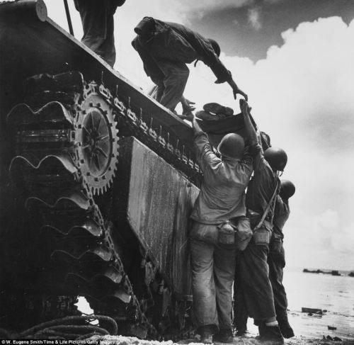 In a photograph taken in a separate battle against Japanese troops in Guam, Smith captures the moment a wounded American Marine is loaded onto an 'alligator' tracked amphibious vehicle for evacuation.