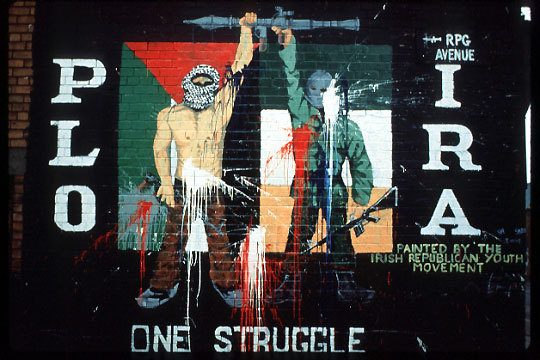 "Mural, Beechmount Avenue, Belfast, 1982 – ""PLO IRA one struggle""; member of Irish Republican Army and member of Palestine Liberation Organization with rifles and rocket launcher, Irish tricolour and Palestinian flag– Painted by the Irish Republican Youth Movement."