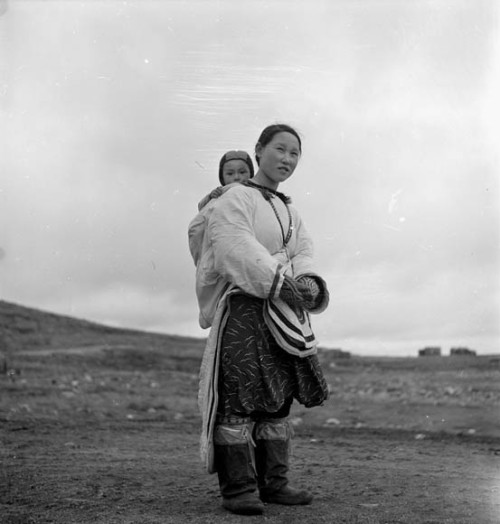 "Unidentified Inuit woman with child. Unknown Location, N.W.T. [Nunavut?], July 1951 Credit: Wilfred Doucette / National Film Board of Canada. Phototheque / Library and Archives Canada / e002265617 Source Extra information provided by ""Anonymous"" in a message: fyi: MIKAN 3603271, pic of Inuit woman wearing amauti is Mrs. Martha Micheal of Iqaluit, Nunavut. She lived in Apex for many years, and is still alive today. -thank you Anonymous!"