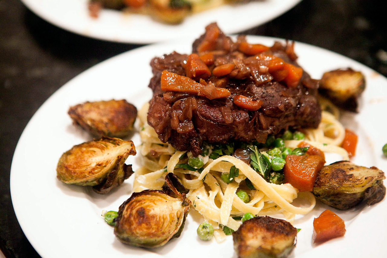 Osso Bucco with Pea, Lemon, Mint and Goat's Cheese Fettuccine, and Crispy Brussel SproutsThis is inspired by the Maggie Beer beef cheeks recipe I made a few weeks ago, it worked pretty well with the osso bucco and I went lighter on some of the ingredients so the veal didn't get overpowered.Ingredients (osso bucco marinade): 4 pieces of thick cut osso bucco 4 roughly chopped garlic cloves 4 sprigs of rosemary 4 bay leaves Rind of 1 orange 2 tbsp juniper berries Salt, pepper, olive oil Toss together the day before cooking.Ingredients (osso bucco): Osso Bucco, removed from marinade 1 chopped onion 2 chopped carrots 1 cup red wine Juice of 1 orange 2 cups of beef stock Sear the osso bucco in a hot pan with a bit of olive oil, then remove, cleaning the pan of most of the oil.  Saute the carrot and onion until soft, seasoning with salt and pepper.  Mix in the liquids and bring to a simmer before adding the osso bucco back in.  Cover and cook on low for 2 hours.  Before serving, remove the osso bucco and reduce the liquid so it forms a sauce.Ingredients (brussel sprouts): 3 cups of brussel sprouts, sliced in half Zest of half a lemon Salt, pepper, olive oil Mix and bake for about 30 minutes, turning halfway through, until crispy.Ingredients (fettuccine): 2 cups of cooked fettuccine 1 cup of frozen peas, defrosted 1/2 cup crumbled goat's cheese Zest and juice of half a lemon 1/2 cup chopped mint leaves Salt and pepper Saute the peas in a bit of olive oil.  Once warm, mix with the rest of the ingredients and season with salt and pepper.