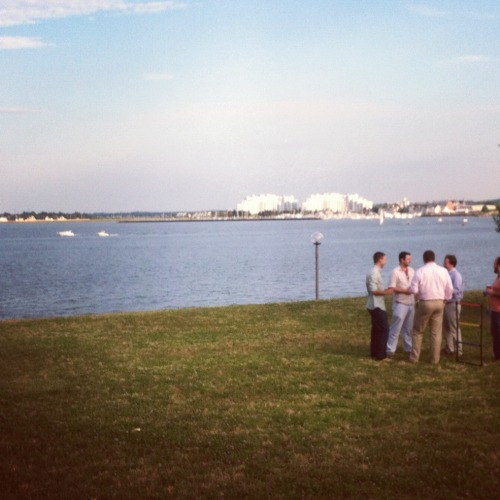 A shot of my company picnic on the waterfront at the JFK Memorial Library in Boston, Mass. About 500 or 600 of my company's employees on the lawn eating BBQ. Not a bad night. Photograph by me, taken with Instagram for iPhone. July 2012.