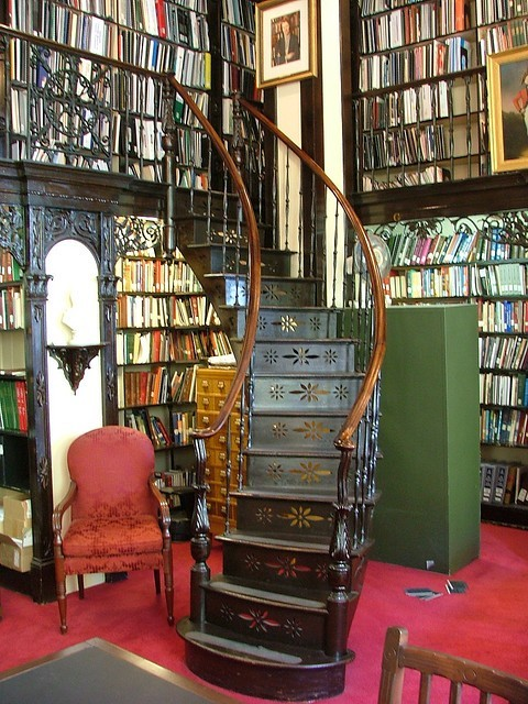 a LOT of books all around a fairy staircase