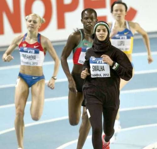 tracktown:  I love this because in the past many muslim girls weren't even allowed to play sports (one of my best friends is muslim, so I know). This is a real breakthrough. Only in the last century were women allowed to participate in marathons. A while ago women weren't allowed to play sports, and many religions and cultures thought it was wrong for a girl to play sports and that their only purpose was to be a housewife and raise the children. At one point women were not even considered persons! This picture really shows what women have been able to do!