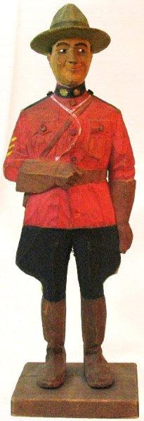 Wood carving of a Royal Canadian Mountie dressed in the traditional red serge. I love the expression on his face