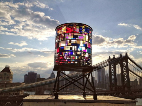 "The New York City skyline is one that you can sit and marvel at for hours on an end. But when you're looking at it from some rooftop in Brooklyn, it's easy to get a glimpse of other random structures in the way. One of these, that Unconsumption is very proud of, is a watertower in Dumbo, Brooklyn. (Dumbo is what the folks of Brooklyn affectionately call the area ""Down Under the Manhattan Bridge Overpass"")  Although this watertower is only for decoration and is not actually in use, it has been built using only recycled plexiglass and steel. Tom Fruin, the designer, collected the plexiglass from various businesses and buildings in New York City. Tom Fruin is known for using recycled materials in his artwork. (via Dumbo's New Recycled Watertower)"