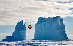 "m0iety:  Michelle Valberg ""This photo was taken on the ice near Arctic Bay last month. As far as we know, it is the highest latitude passenger flight on a hot air balloon ever. It was quite the sight to see a hot air balloon fly between the iceberg columns — it is one iceberg but looks like two."""