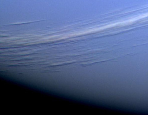solari-s:  Two Hours Before Neptune - Two hours before closest approach to Neptune in 1989, the Voyager 2 robot spacecraft snapped this picture. Clearly visible for the first time were long light-colored cirrus-type clouds floating high in Neptune's atmosphere. Shadows of these clouds can even be seen on lower cloud decks. Most of Neptune's atmosphere is made of hydrogen and helium, which is invisible. Neptune's blue color therefore comes from smaller amounts of atmospheric methane, which preferentially absorbs red light. Neptune has the fastest winds in the Solar System, with gusts reaching 2000 kilometers per hour. Speculation holds that diamonds may be created in the dense hot conditions that exist under the cloud tops of Uranus and Neptune. (via APOD)
