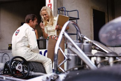 paddock gossip …Sally Courage talking with Bruce McLaren, 1969 Italian Grand Prix, Monza