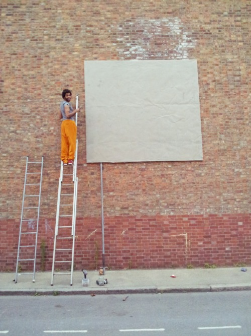 Duval Timothy installing the screen for BAG DROP screening on Watergate street, Deptford 2012. Deptford X Fringe festival.