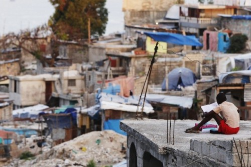 A boy reads a book on the roof of his home during sunrise in Port-au-Prince on March 17, 2011.  Only 49 percent of Haitian adults are literate.  (Photo: REUTERS/Shannon Stapleton)