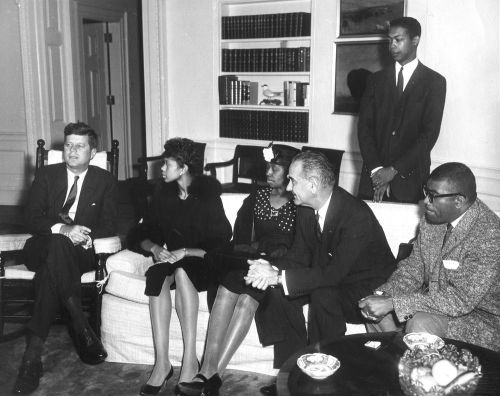 """usnatarchives:  Olympic track and field gold medalist Wilma Rudolph was invited to the White House after her victories in the 1960 Olympics. In this photograph, she is in the Oval Office with President John F. Kennedy. At the 1960 Olympics in Rome, Rudolph became """"the fastest woman in the world"""" and the first American woman to win three gold medals in one Olympics. She won the 100- and 200-meter races and anchored the U.S. team to victory in the 4 x 100-meter relay. The first integrated events in Rudolph's hometown of Clarksville, Tennessee, were the parade and banquet given in honor of her victories. Rudolph died of cancer in 1994 at age 55. You can read more about her life and career here. Also in the photo are Rudolph's mother Blanche Rudolph, Robert Logan (standing), Vice President Johnson, and Edward Temple, the coach of the 1960 women's Olympic track team."""
