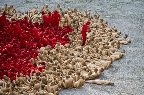 "The Naked World of Spencer Tunick: For 20 years now, New York-based photographer Spencer Tunick has been creating human art installations all over the world, calling together volunteers by the hundreds or thousands, asking them to remove their clothes, and photographing them in massive groups. His philosophy is that ""individuals en masse, without their clothing, grouped together, metamorphose into a new shape."" He aims to create an architecture of flesh, where the masses of human bodies blend with the landscape, or juxtapose with architecture. Collected here are images from several of his installations as they were being composed. Warning: The following photos all depict naked human bodies, and are not screened out. The nudity is central to Tunick's art. [33 photos]"