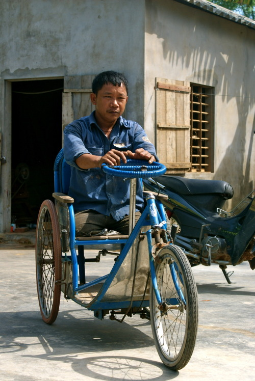 A Vietnamese landmine victim on his three-wheel in front of his carpenter workshop.