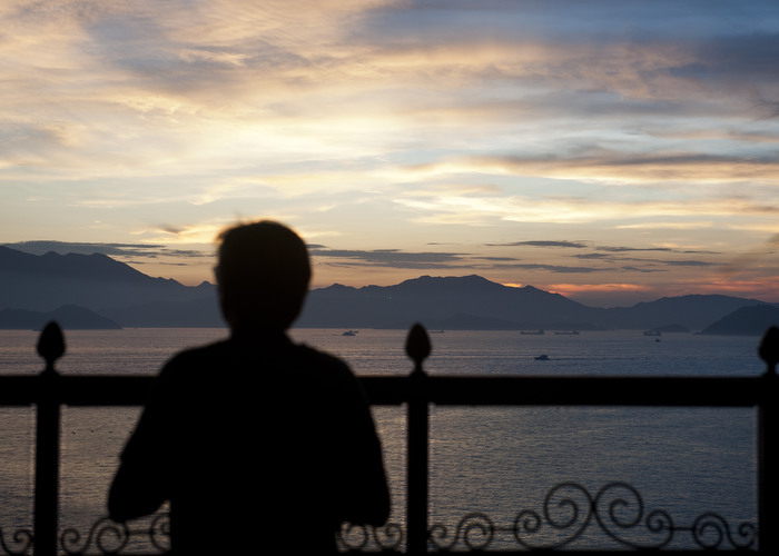 HONG KONG: July 29, 2012 — A man observes the clear sky sunset after Typhoon Vicente in Hong Kong Sunday, July 29, 2012. More than 100 people were injured and trees were ripped from the ground as a typhoon lashed Hong Kong packing winds in excess of 140 kilometres (87 miles) an hour, officials said as authorities raised the typhoon warning to the most severe level of 10 for the first time since 1999. (Photo by JUSTIN CHIN)