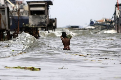 inothernews:  DIRE STRAIT  A boy waded through rising seawater in Navotas, Philippines, Tuesday. Fierce wind and heavy rain from the slow-moving, offshore Typhoon Saola battered the Philippines again Tuesday, killing at least 10 people and displacing 145,000 others. (Photo: Francis R. Malasig / EPA via The Wall Street Journal)