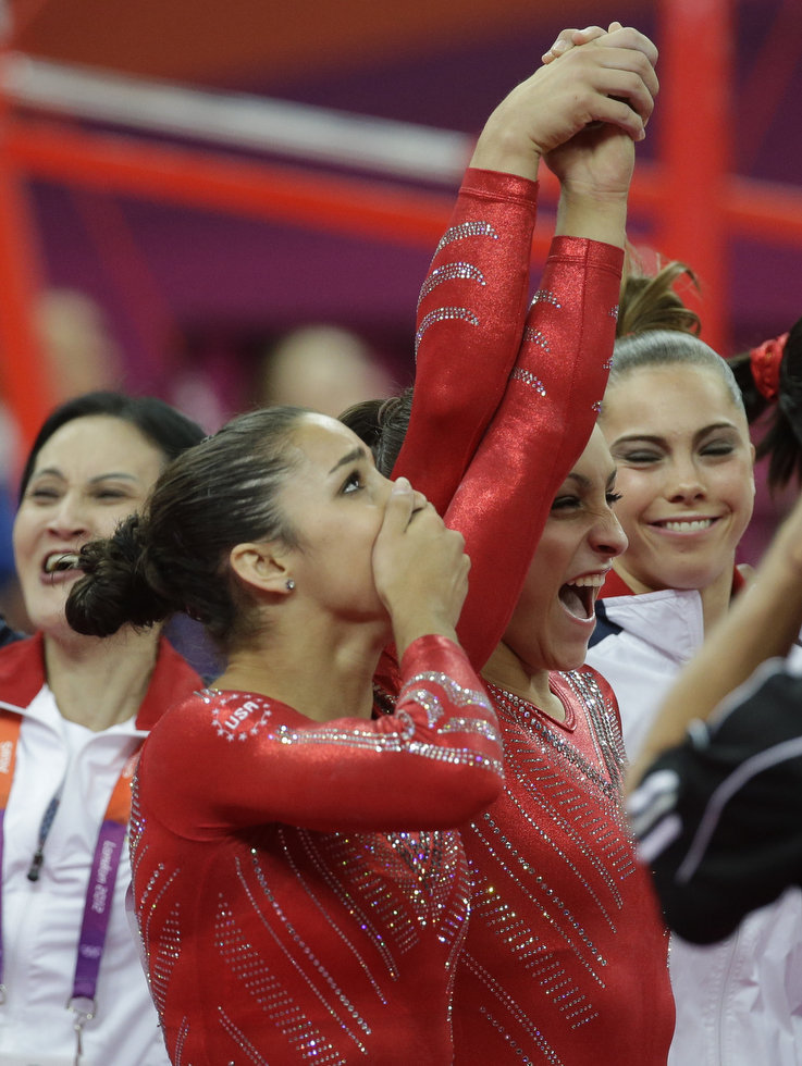 U.S. gymnast Jordyn Wieber, center, lifts up the hand of teammate Alexandra Raisman, as they celebrate along with McKayla Maroney after being declared winners of the gold medal during the Artistic Gymnastic women's team final at the 2012 Summer Olympics, Tuesday, July 31, 2012, in London.