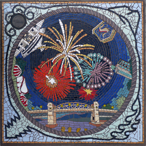 Fireworks Over English Bay, another tile mosaic by Bruce Walther. This particular mosaic at Pacific and Burrard was created in 2008 and was a Downtown Vancouver Business Improvement Association initiative, with funding assistance provided by the 2010 Cultural Olympiad. From the DVBIA pamphlet:  The Downtown Vancouver Business Improvement Association's public art project beautifies downtown streets with 18 original tile mosaics, each measuring nine square feet and permanently installed in city sidewalks throughout the DVBIA's 90-block area. The mosaics celebrate the diversity of Vancouver's culture, sports, architecture, natural beauty and personalities. Accomplished local mosaic artists Liz Calvin and Bruce Walther designed, produced and installed all the tiles.