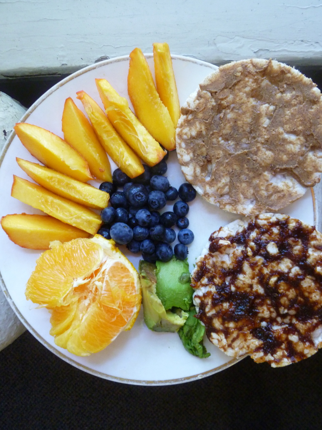 morning meals: peach, orange, blueberries, avocado and almond and fig butter spread across 2 plain rice cakes