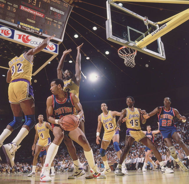 Adrian Dantley looks for space amidst the outstretched arms of Magic Johnson and James Worthy during Game 1 of the 1988 NBA Finals. The Pistons would win the game 105-93 but lose the series in seven. (Peter Read Miller/SI)   GALLERY: Iconic Photos of the Los Angeles Lakers | Detroit Pistons