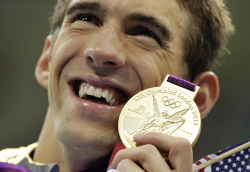 United States' Michael Phelps poses with his gold medal for the men's 4x200-meter freestyle relay